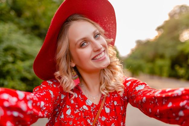 Jolie femme souriante blonde élégante en chapeau de paille rouge et blouse tenue de mode d'été prenant selfie photo