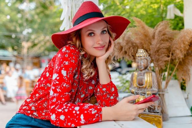 Jolie femme souriante blonde élégante en chapeau rouge de paille et tenue de mode d'été chemisier tenant à l'aide de café de téléphone intelligent