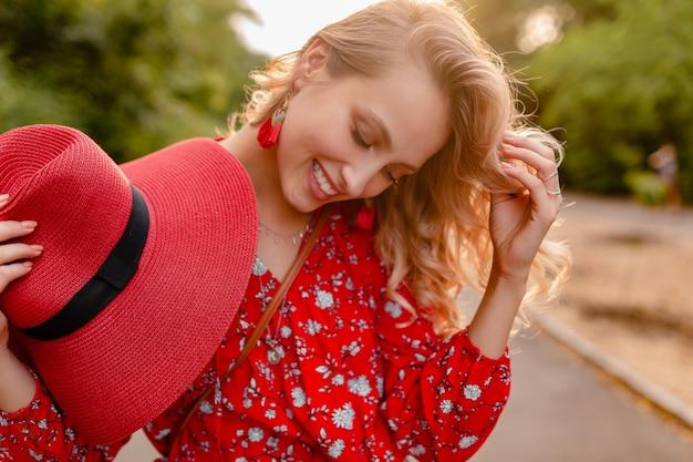 Jolie femme souriante blonde élégante en chapeau rouge de paille et tenue de mode d'été chemisier
