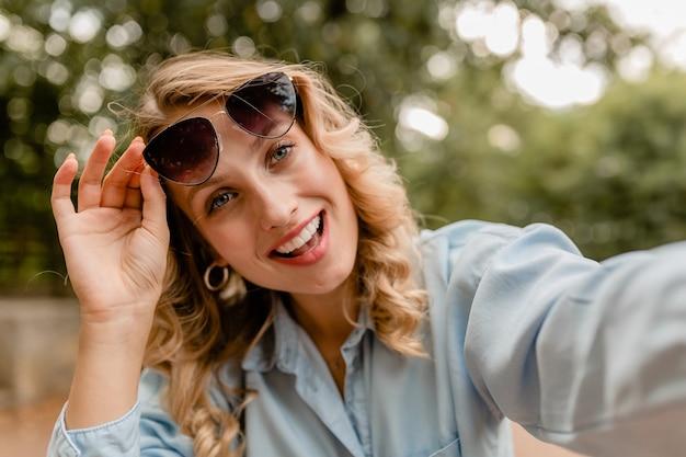Jolie femme souriante blonde marchant dans le parc en tenue d'été prenant selfie photo sur téléphone