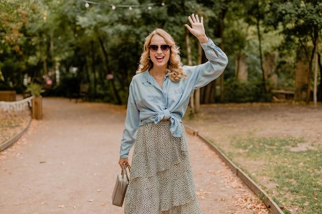 Jolie femme souriante blonde marchant dans le parc en tenue d'été