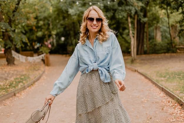 Jolie femme souriante blonde qui marche dans le parc en tenue élégante