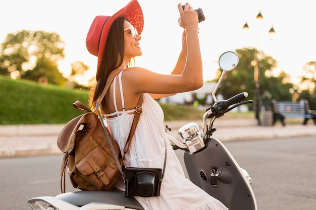 Jolie femme souriante à cheval sur la moto dans la rue en tenue de style estivale portant une robe blanche et un chapeau rouge voyageant avec sac à dos en vacances, prenant des photos sur un appareil photo vintage