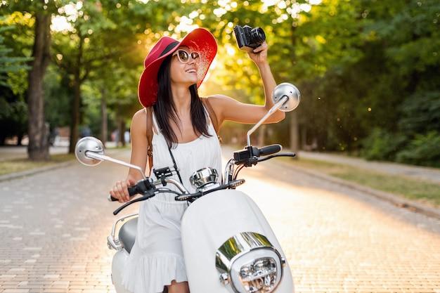 Jolie femme souriante à cheval sur une moto dans la rue en tenue de style estivale portant une robe blanche et un chapeau rouge voyageant en vacances, prenant des photos sur un appareil photo vintage