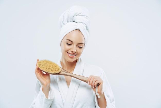 Jolie femme souriante concentrée vers le bas, tient la brosse de bain, prend une douche, se soucie de l'hygiène, porte une serviette sur la tête, une robe blanche douce, pose sur fond blanc. concept de femmes et de propreté