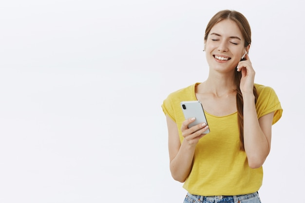Jolie femme souriante dans des écouteurs, écouter de la musique ou un podcast, à l'aide de smartphone
