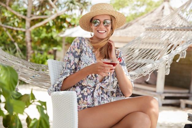 Jolie femme souriante dans des tons à la mode bénéficie d'un bon repos en plein air avec un cocktail frais, pose contre un hamac, heureuse de se retrouver entre amis et de faire une pause après le travail. gens, loisirs et style de vie