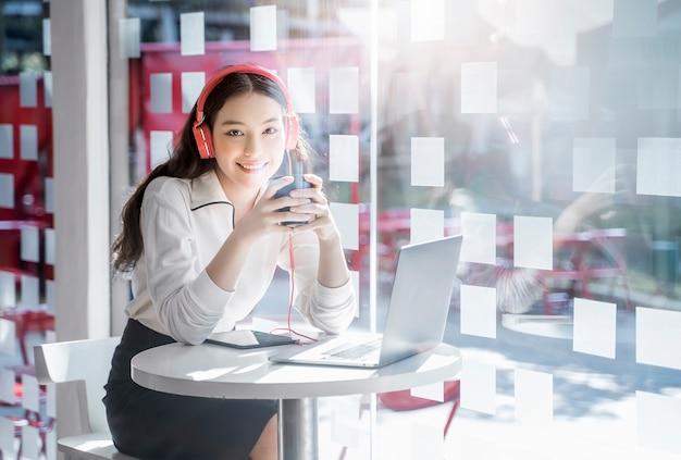 Jolie femme souriante écoutant de la musique avec des écouteurs avec plaisir au bureau de coworking