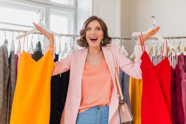 Jolie femme souriante élégante choisissant des vêtements dans un magasin de vêtements
