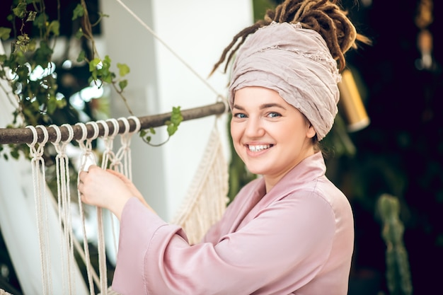 Jolie femme souriante faisant du tissage en macramé