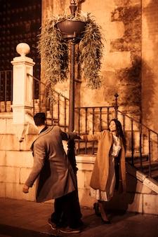 Jolie femme souriante et jeune homme tourbillonnant autour d'un lampadaire