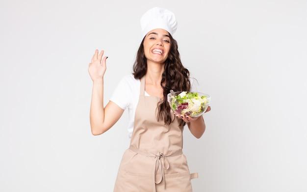 Jolie femme souriante joyeusement, agitant la main, vous accueillant et vous saluant portant un tablier et tenant une salade