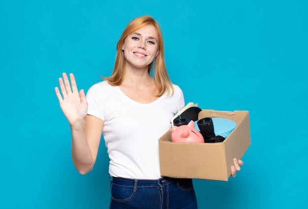 Jolie femme souriante joyeusement et joyeusement, agitant la main, vous accueillant et vous saluant, ou vous disant au revoir