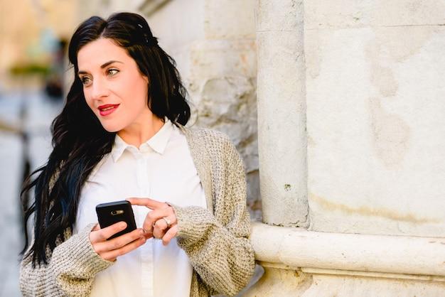 Jolie femme souriante lorsqu'elle reçoit de bonnes nouvelles sur son téléphone portable dans une rue.