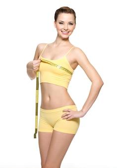 Jolie femme souriante mesurant la poitrine avec le type de mesure - isolé sur blanc
