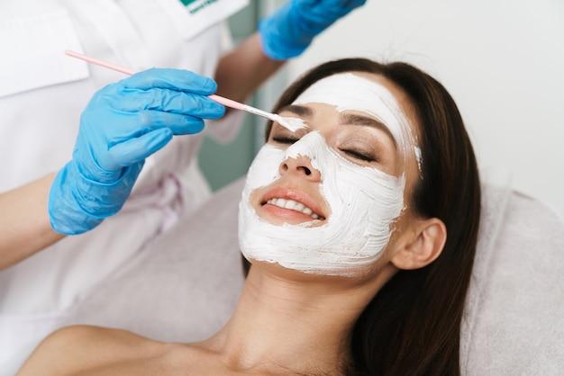 Jolie femme souriante obtenant une procédure cosmétique par un spécialiste en position couchée dans un salon de beauté