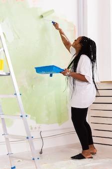 Jolie femme souriante peinture mur intérieur de la maison avec rouleau à peinture