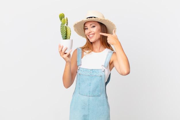 Jolie femme souriante pointant avec confiance vers son propre large sourire et tenant une plante décorative de cactus