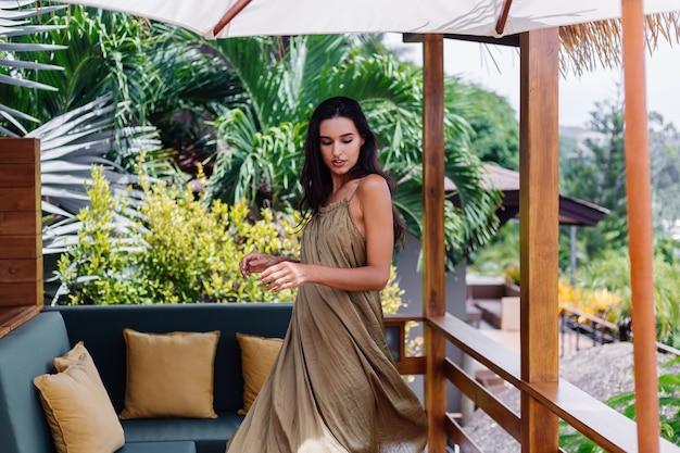 Jolie femme souriante positive européenne en robe de vol d'été à la lumière du jour naturelle à la terrasse de la villa bénéficiant de belles vacances, canapé extérieur avec oreillers sur tropical.