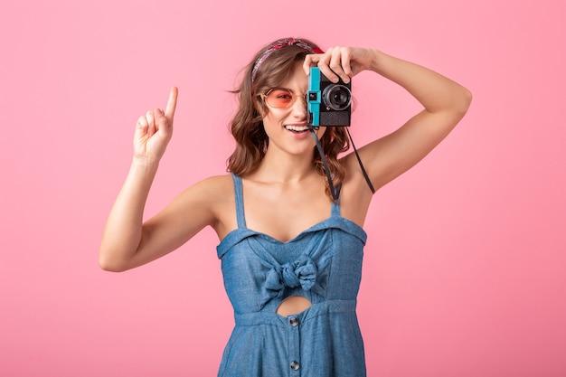 Jolie femme souriante prenant une photo sur un appareil photo vintage, pointant le doigt vers le haut, portant une robe en jean et des lunettes de soleil isolées sur fond rose