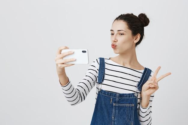 Jolie femme souriante prenant selfie sur smartphone, montrer le signe de la paix