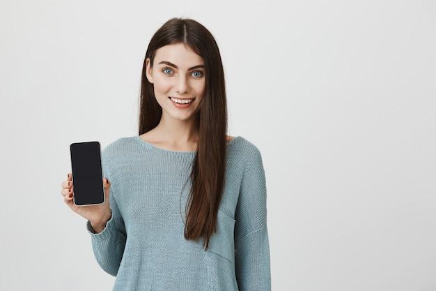 Jolie femme souriante promouvoir l'application, afficher l'écran du smartphone