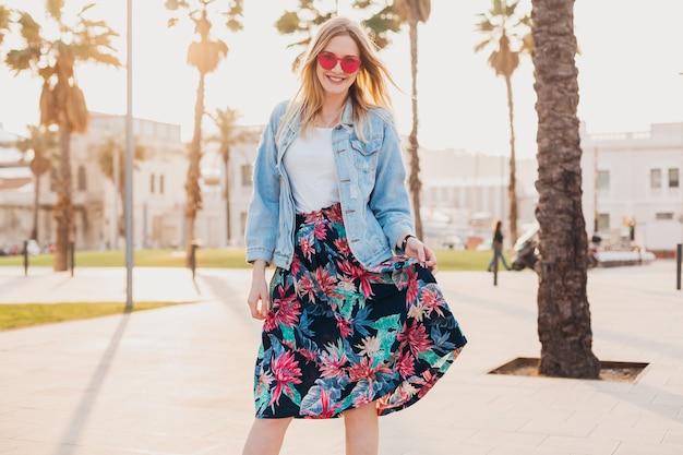 Jolie femme souriante qui marche dans la rue de la ville en jupe imprimée élégante et veste oversize en denim portant des lunettes de soleil roses, tendance de style d'été