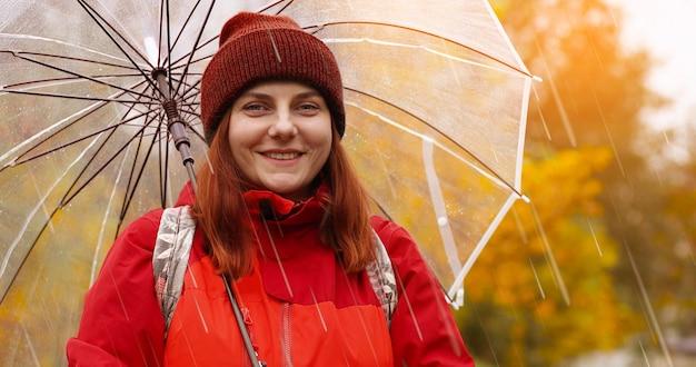 Une jolie femme souriante de race blanche avec un sac à dos et une veste rouge se promène dans les rues humides et pluvieuses sous un parapluie transparent