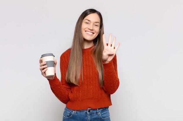 Jolie femme souriante et à la recherche amicale, montrant le numéro quatre ou quatrième avec la main en avant
