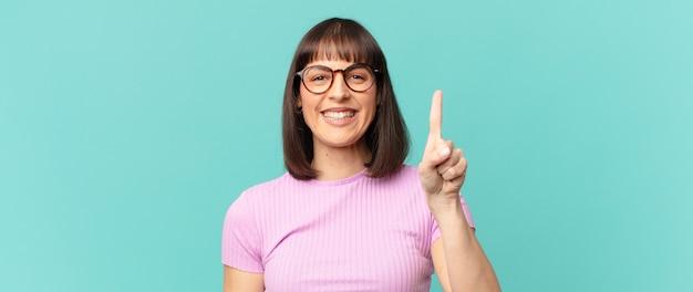 Jolie femme souriante et semblant amicale, montrant le numéro un ou le premier avec la main vers l'avant, compte à rebours
