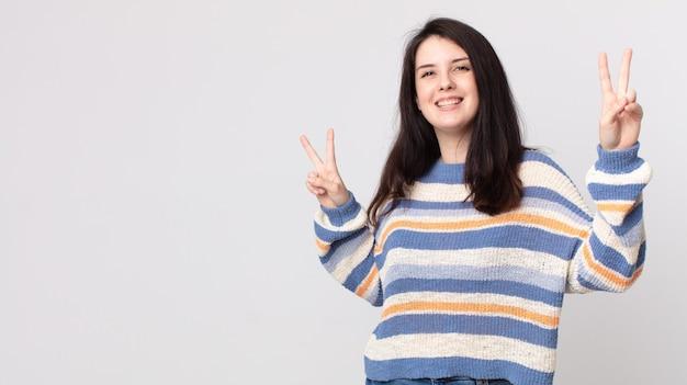 Jolie femme souriante et semblant heureuse, amicale et satisfaite, gesticulant la victoire ou la paix avec les deux mains