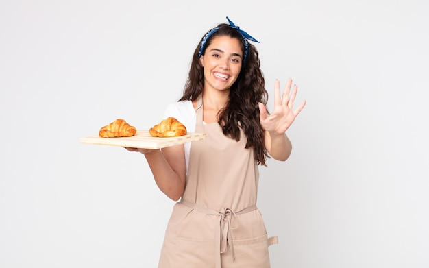 Jolie femme souriante et sympathique, montrant le numéro cinq et tenant un plateau de croissants