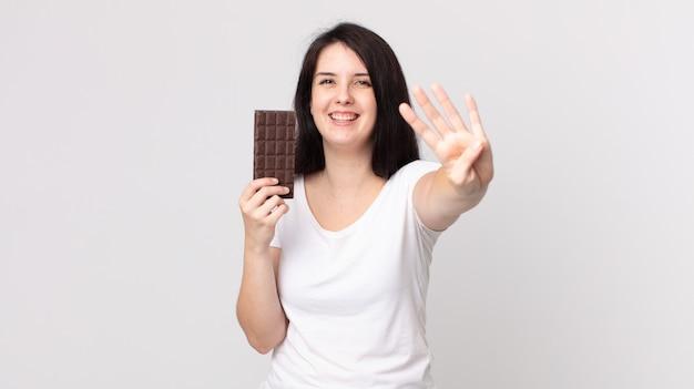 Jolie femme souriante et sympathique, montrant le numéro quatre et tenant une barre de chocolat