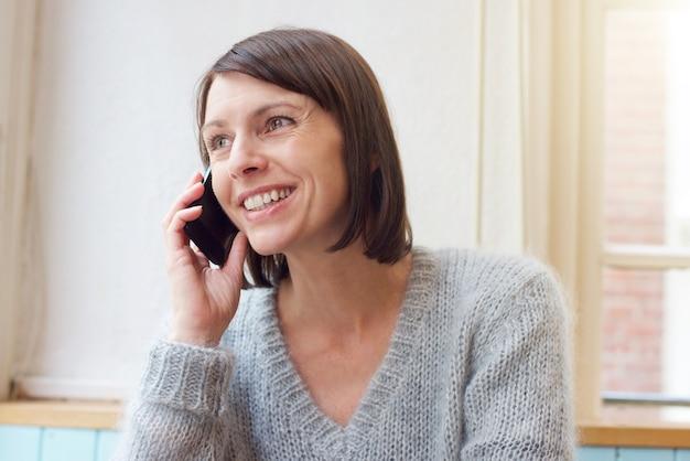 Jolie femme souriante avec téléphone portable à la maison