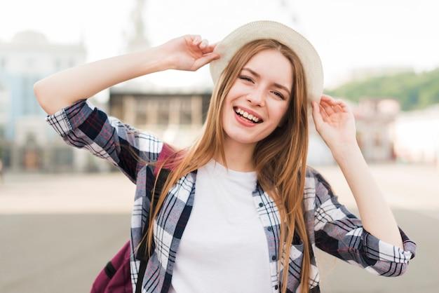 Jolie femme souriante tenant un chapeau et posant