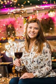Jolie femme souriante tenant un verre de vin dégustant une fête