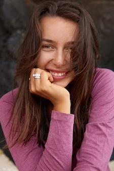 Jolie femme souriante tient la main sur le menton, a les cheveux foncés