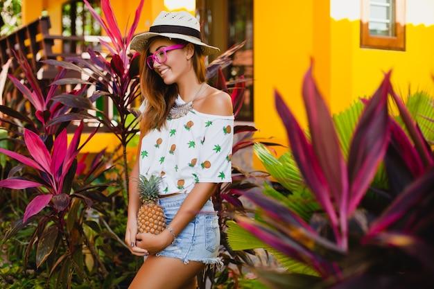 Jolie femme souriante en vacances en t-shirt imprimé mode d'été chapeau de paille, mains tenant ananas