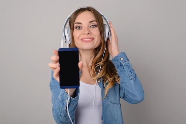 Jolie femme avec un sourire à pleines dents écoutant de la musique via des écouteurs et montrant un écran noir vide de son téléphone portable ; isolé sur fond gris