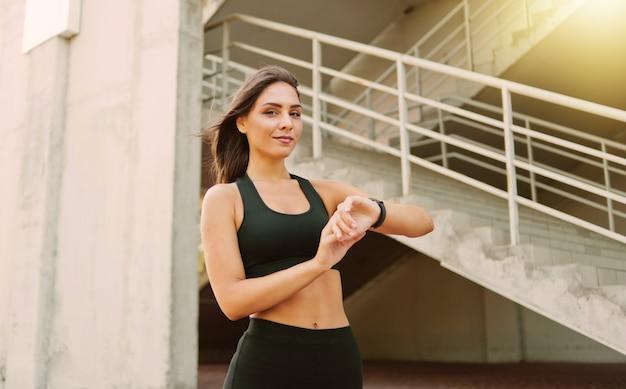 Jolie femme de sport en vêtements de sport utilise une montre intelligente à l'extérieur en milieu urbain