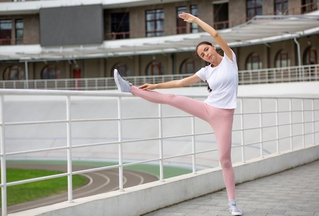 Jolie femme sportive bronzée qui s'étire avant de courir en appuyant sa jambe sur la barrière. espace pour le texte