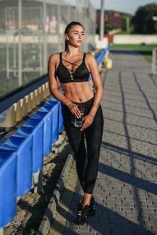 Jolie femme sportive avec un casque sans fil et une bouteille d'eau en écoutant de la musique tout en s'entraînant sur un terrain de sport en plein air.
