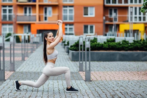 Jolie femme sportive dans la nature. femme, brune en forme parfaite faisant des squats.