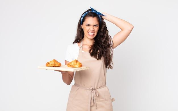 Jolie femme stressée, anxieuse ou effrayée, les mains sur la tête et tenant un plateau de croissants