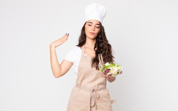 Jolie femme stressée, anxieuse, fatiguée et frustrée portant un tablier et tenant une salade