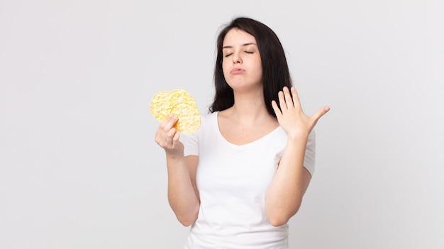 Jolie femme stressée, anxieuse, fatiguée et frustrée et tenant un régime de gâteaux de riz