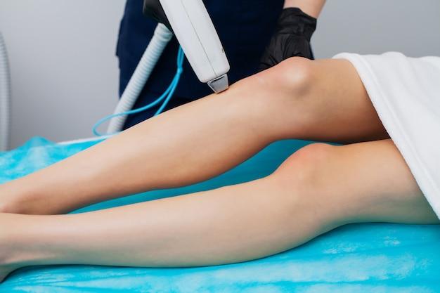 Jolie femme en studio de beauté obtenant une procédure d'épilation au laser