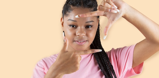 Jolie femme sud-américaine, fait des gestes avec ses doigts pour prendre une photo