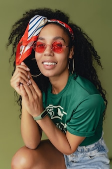 Jolie femme en t-shirt et short élégant tenue hipster sur le mur vert du studio