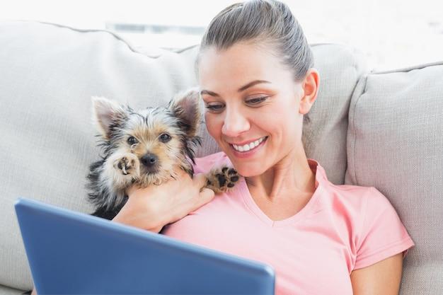 Jolie femme avec tablette avec son yorkshire terrier